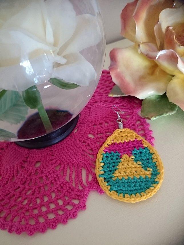 Ett flerfärgsvirkat örhänge i oval form i färgerna gult, grönt och rosa. Örhänget ligger på en rosa virkad duk bredivd ett rosarie och en porslinsros.