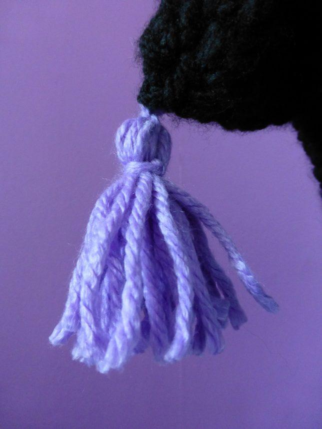 Den lila toffsen på den virkade mössan