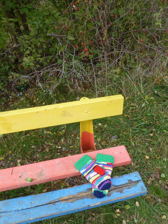 Virkade vantar ligger på en parkbänk som är målad i grönt, rött och blått