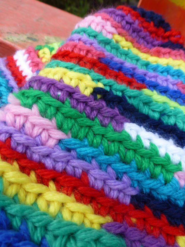 Närbild på virkade vantar i flera olika färger